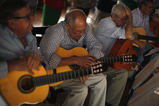 Pensioners take a break from rehearsing songs on Spanish guitars at a seniors centre during the International Day of Older Persons in Ronda