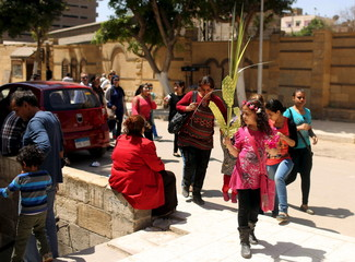 An Egyptian Coptic Christian girl carries a palm decoration as people enter a church during Palm Sunday in Old Cairo