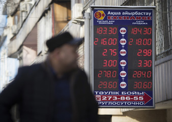 A man walks past a board showing currency exchange rates in Almaty