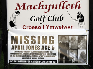 A poster giving details of missing girl April Jones is attached to a golf club sign in Machynlleth, Mid Wales