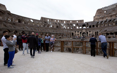 Britain's Prince Harry listens to an Italian guide as he tours the Colosseum in Rome