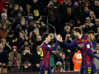 Barcelona's Messi celebrates with team mate Pique after scoring his third goal against Espanyol during their Spanish first division soccer match at Nou Camp stadium in Barcelona
