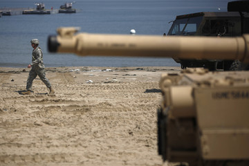 "A U.S. Marine walks on a beach during the CJLOTS exercise, as a part of the annual joint U.S. and South Korean exercise ""Foal Eagle"" in Pohang"