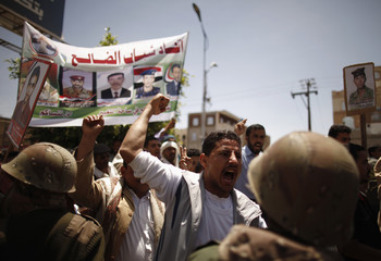 Protesters shout slogans as army soldiers block them in front of the house of Yemen's President Hadi as they march to demand a trial for former President Saleh in Sanaa