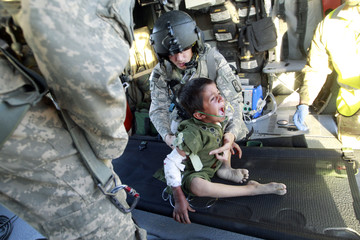 U.S. flight medic Sergeant Raines and Crew Chief SSG Meece pass an Afghan child to hospital staff folowing a Medevac flight in Helmand province