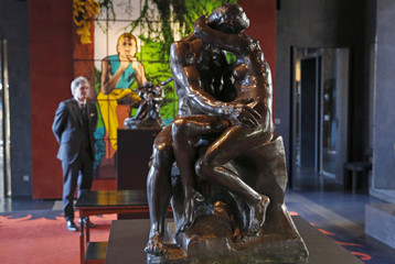"Auctioneer Alexandre Giquello looks at the sculpture ""Le Baiser"" which is part of an exceptional sale of five remarkable bronzes by the French sculptor Auguste Rodin, displayed in Paris"