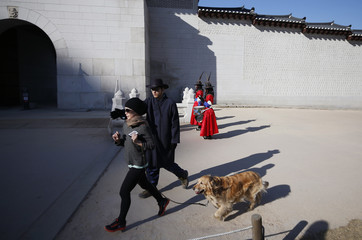 A tourist guide stops a woman with a dog from crossing the main entrance of Gyeongbok Palace as workers wearing traditional dress attend the daily reenactment for the changing of the Royal Guards on a sunny winter day in Seoul