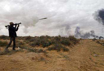 A rebel fighter fires a rocket-propelled grenade launcher during a battle on the road between Ras Lanuf and Bin Jawad