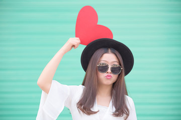 Asian Chinese woman and Valentines day.Young woman holding a red heart shape card with green background.