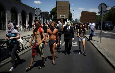 Demonstrators wearing Guy Fawkes masks march outside the Spanish Labour Ministry during an unemployment protest in Madrid