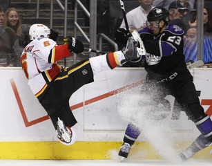 Kings' Brown checks Flames' Giordano to the ice during the second period of their NHL hockey game in Los Angeles