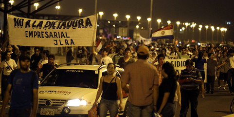 Demonstrators march as they protest against the rise in public transport fares, near the Government Palace in Asuncion