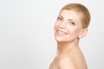 Happy health. Horizontal studio portrait of a gorgeous mature woman smiling happily looking over the shoulder copyspace on the side