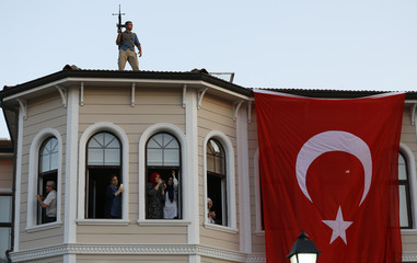 People try to take pictures of Turkish President Tayyip Erdogan walking through the crowd of supporters, as a security officer stands on the roof in Istanbul
