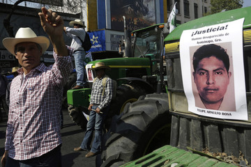 Farmers stand outside the Interior Ministry with their tractors and pictures of the 43 missing trainee teachers the during a protest in Mexico City