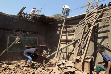 Residents of Nagarote town repair the roof of their house that was damaged in an earthquake in Nagarote