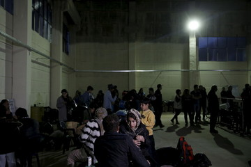 Refugees and migrants wait to be registered at the migrant registration centre on the Greek island of Chios
