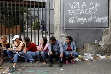 """People sit next to graffiti that reads, """"Venezuela without shortages, 6E the change arrives"""", while they line up to try to buy cooking oil and milk, outside a supermarket in Caracas"""