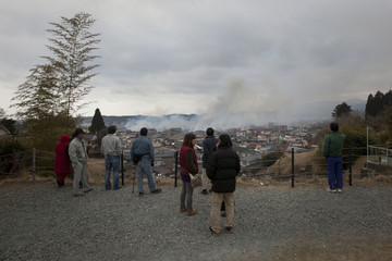 Residents stand along a hillside looking over Kesennuma City as it burns days after the area was devastated by a magnitude 9.0 earthquake and tsunami