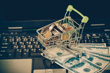 Small shopping cart contains coins on laptop and working space on wooden .