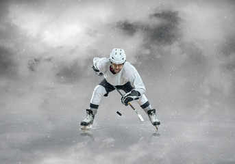 Ice hockey player in sport action on the ice under sky