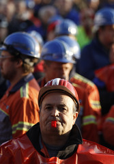 A steel worker of 'ThyssenKrupp Nirosta' blows a whistle during a warning strike in Krefeld