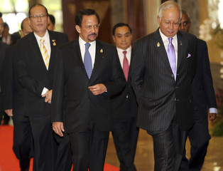 Brunei's Sultan Hassanal Bolkiah walks with Malaysian PM Razak, Philippines' President Aquino and Laos' PM Thammavong to a plenary meeting at Jakarta Convention Centre