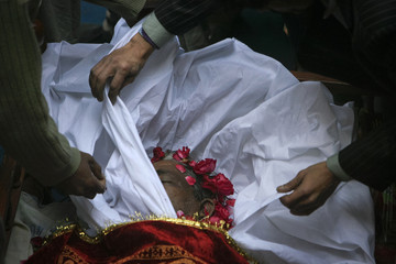 Rose petals crown the face of 62-year-old heart patient Chaudhry Mohammad Gulab as his family members prepare him for burial in Lahore
