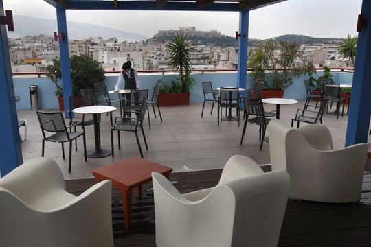 An employee of the Imperial hotel cleans tables at the hotel's roof garden with the Acropolis hill in the background during the last day of its operation in Athens