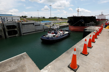 A tugboat drags a Post-Panamax cargo ship during the first trial run at the new sets of locks on the Atlantic side of the Panama Canal