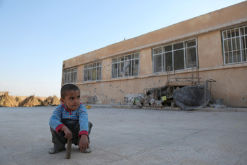 An internally displaced boy sits on the ground near a school in the village of al-Heesha in Raqqa district after it was captured from Islamic State, north of Raqqa city