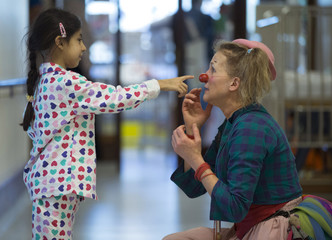 Girl touches the red nose of a Belgian clown at the pediatric department of the Hopital Erasme at the ULB in Brussels