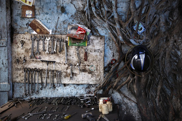A mechanic's tools are seen on a table and on the wall as a tree grows beside, in an auto workshop in Mumbai