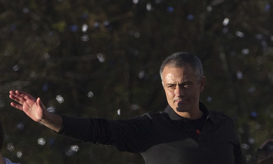 Real Madrid's coach Mourinho gestures as he walks around Cibeles statue in central Madrid