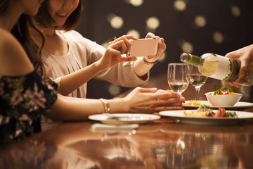 Women are taking photos of wine at the bar