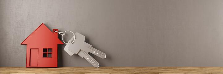 Schlüssel mit Haus an Wand gelehnt
