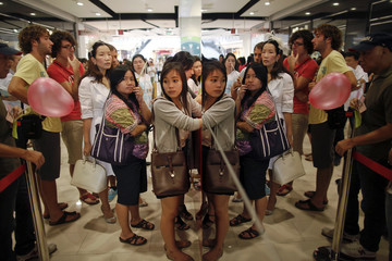 Shoppers wait in line for promotion coupons during the re-opening ceremony of Bangkok's Central World shopping mall