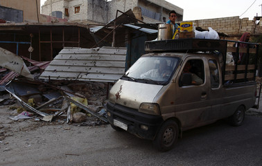 People leaving in a truck drive past a destroyed buildings during clashes between Syrian President Bashar al-Assad's forces and the Free Syrian Army in Attarib
