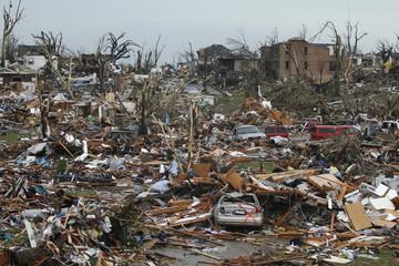 Destroyed vehicles and buildings litter a neighborhood after a devastating tornado hit Joplin