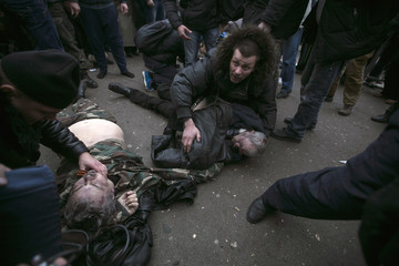 Injured men receive medical treatment after they were injured in a stampede during clashes in Simferopol