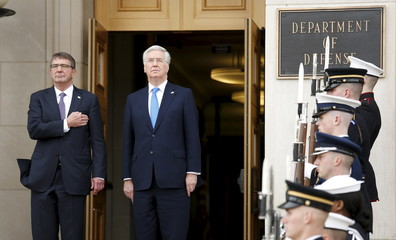 U.S. Defense Secretary Ash Carter and his British counterpart Michael Fallon listen to national anthems upon Fallon's arrival at the Pentagon in Washington