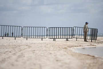 A tourist stands along of a beach near where the Rio Group Summit will take place in Cancun