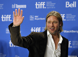 U.S. actor Brad Pitt waves at the end of the news conference for the film 'Moneyball' at the Toronto International Film Festival