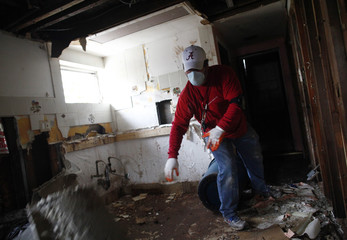 A man removes drywall from the basement of a home damaged by Hurricane Sandy in the Staten Island borough of New York