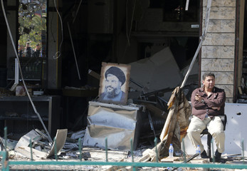 A man sits near a picture of Lebanon's Hezbollah leader Nasrallah  in front of a damaged shop in Beirut