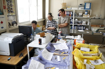 Vucetic checks identification results as Catic and Jakubovic wait at a forensic laboratory in Tuzla