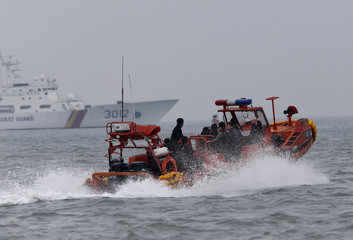 South Korean rescue workers travel in a boat near the site where capsized passenger ship Sewol sank last Wednesday, in the sea off Jindo