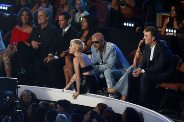"""Miley Cyrus waits on the side of stage as a spokesperson named Jesse accepts the award for video of the year for her song """"Wrecking Ball"""" during the 2014 MTV Video Music Awards in Inglewood"""