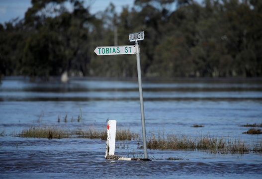A street sign is partially submerged after a natural disaster zone was declared due to flooding from heavy rain in the midwestern New South Wales town of Forbes