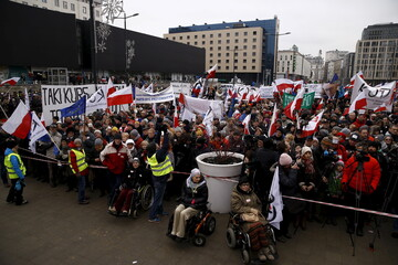 People gather during an anti-government demonstration for free media in front of the Television headquarter in Warsaw